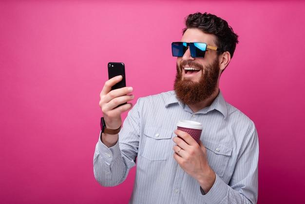 若いひげを生やしたヒップスター男がピンクの背景に彼のコーヒーカップでselfieを取って。