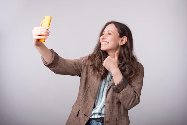 スマートフォンでselfieを取り、親指を現して魅力的な若いビジネス女性の肖像画。