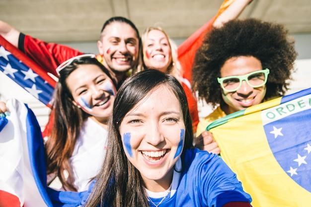 Selfieを取って混合のフットボールのファンのグループ