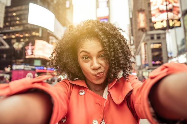 ニューヨーク、タイムズスクエアでselfieを取る若いアメリカ人女性