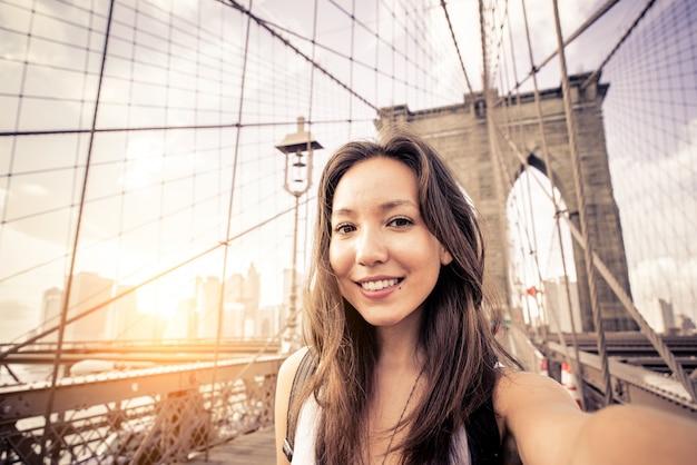 ブルックリンブリッジでselfieを取る女性