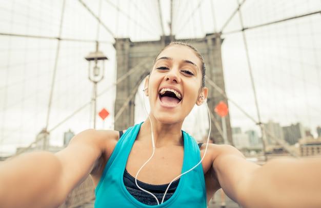 ブルックリン橋でselfieを取っているランナーの女の子