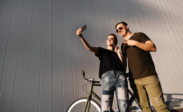 スタイリッシュな魅力的な女性と男が屋外で自転車で立って、携帯電話を使用してselfie写真を作りながらピースサインを見せています。底面図
