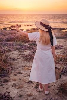海の夕日を楽しんで、selfieを取って白いドレスを着た女性