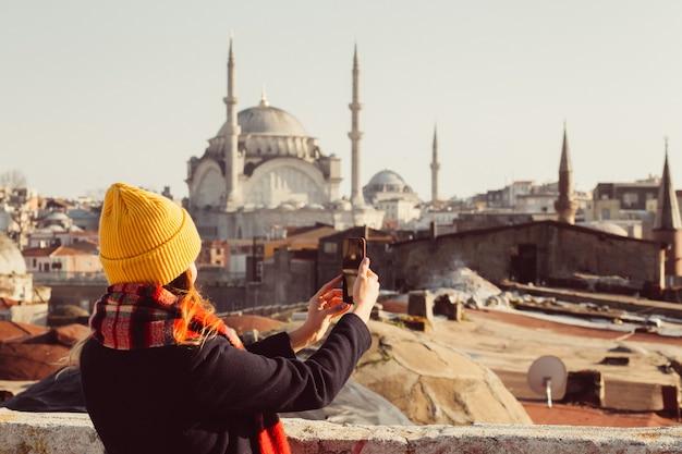 ブロンドの女性は、トルコ、イスタンブールのグランドバザールの屋根の上の電話で写真を作成します。黄色い帽子の少女は、晴れた秋の日にselfieを取ります。旅行者の女の子は、冬のイスタンブールを歩きます。