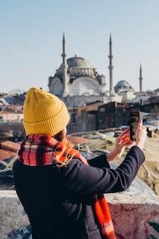 Белокурая женщина делает фото на телефон на крыше гранд базар, стамбул, турция. девушка в желтой шляпе принимает selfie в солнечный осенний день. путешественник девушка гуляет по зимнему стамбулу.