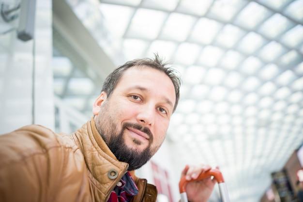 Selfieを取って空港でスーツケースを持つ男