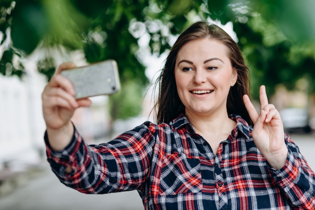 カメラでselfieを作る公園で幸せな若い女。