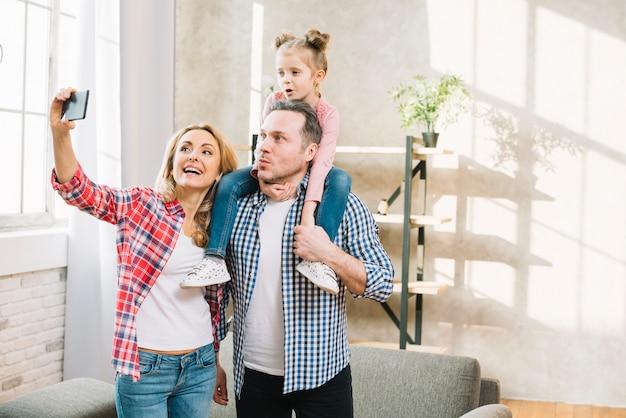 幸せな家族の自宅で携帯電話でselfieを引き継ぐ