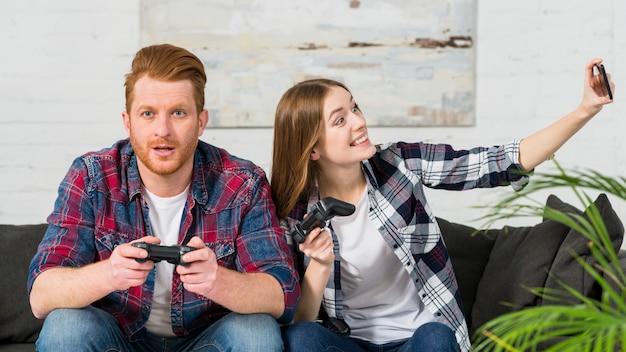 スマートフォンでselfieを取って彼女のボーイフレンドと一緒にビデオゲームを遊んで笑顔の女性