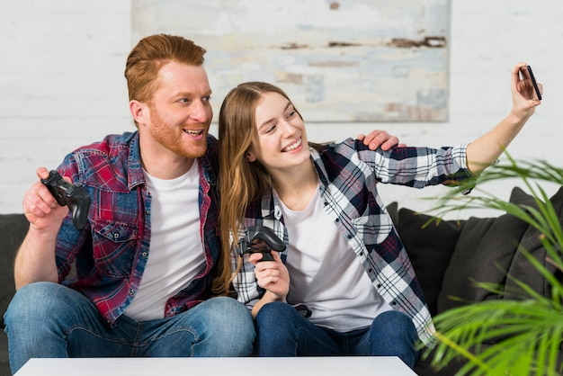 携帯電話でselfieを取ってビデオゲームコントローラーを保持している笑顔の若いカップルの肖像画