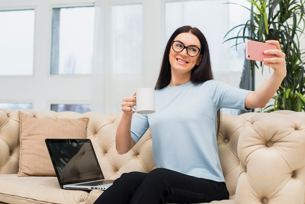 ソファでコーヒーを飲みながらselfieを取っている女性