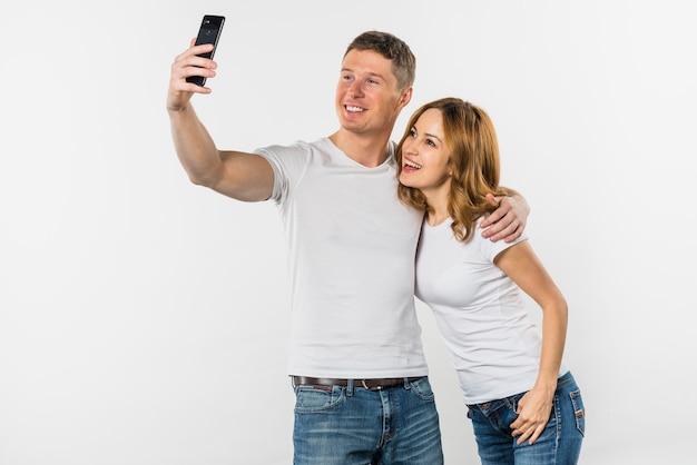 若いカップルが白い背景で隔離の携帯電話にselfieを引き継ぐ