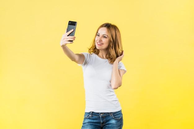 黄色の背景に携帯電話でselfieを取って幸せな若い女