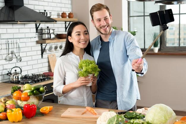 台所で携帯電話でselfieを取って笑顔のカップルの正面図