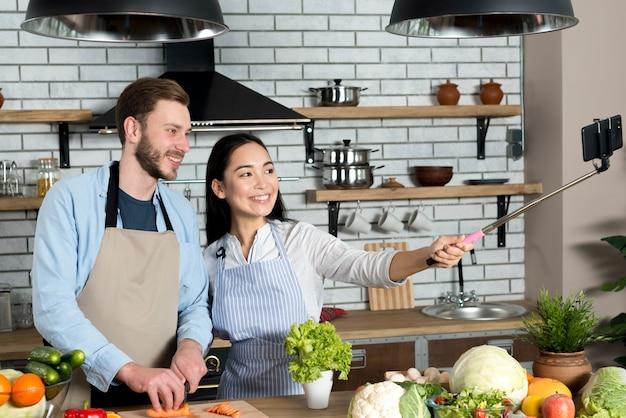 アジアの女性が台所のカウンターの後ろに立っている彼女の若い夫と携帯電話でselfieを取って