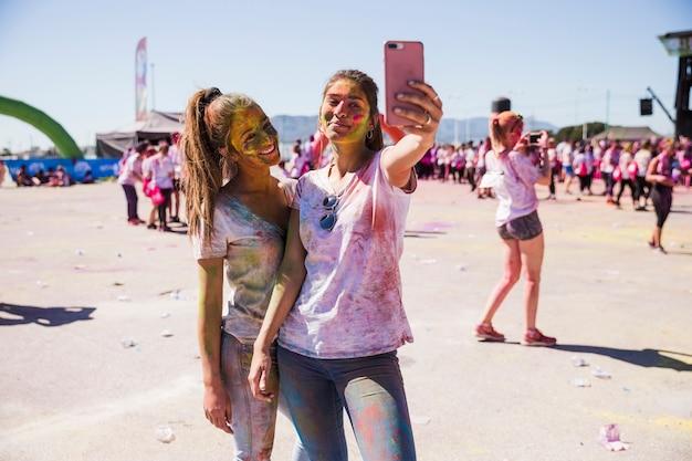 携帯電話でselfieを取って笑顔の若い女性の肖像画