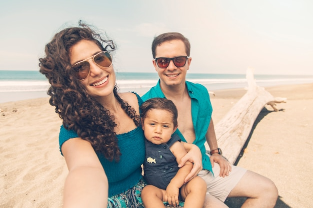 Счастливые родители, улыбаясь и принимая selfie на пляже.