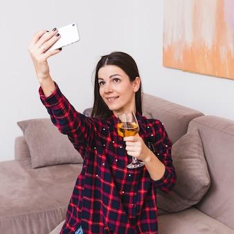 携帯電話でselfieを取って手にワイングラスを保持している若い女性