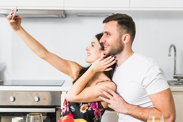 台所で携帯電話でselfieを取って愛する若いカップル