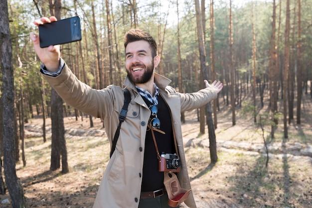 森の中の携帯電話でselfieを取って男性ハイカー