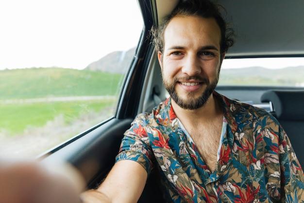 笑みを浮かべて男が車の中でselfieを取って