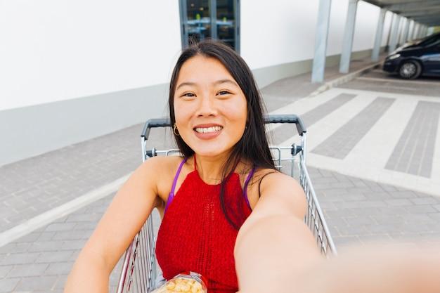 アジアの女性のショッピングトロリーでselfieを取って