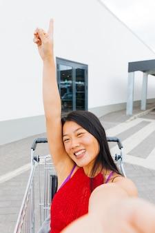 アジアの女性がポーズをとって、ショッピングトロリーでselfieを取って