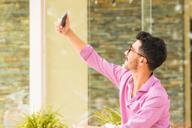 携帯電話でselfieを取ってピンクのシャツでハンサムな男の肖像
