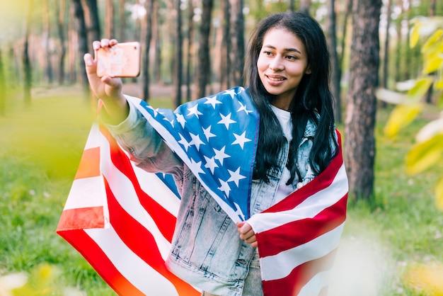 Selfieを取ってフラグを持つ女性
