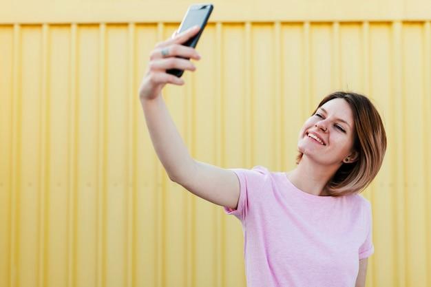 携帯電話でselfieを取って段ボールの黄色い金属シートに対して立っている笑顔の若い女性