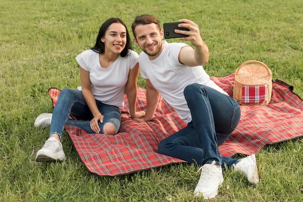 ピクニック毛布で、selfieを取ってカップル