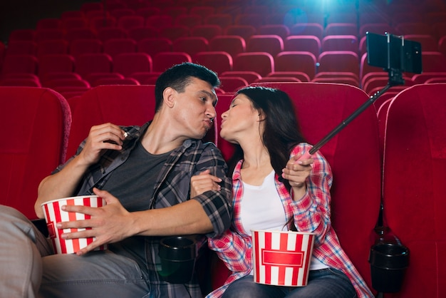 カップルがキスをし、映画館でselfieを引き継ぐ