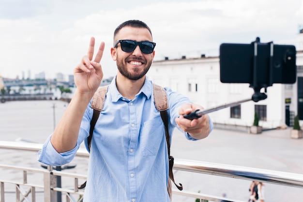 携帯電話で勝利のジェスチャーでselfieを取って笑みを浮かべて男