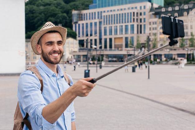 スマートフォンでselfieを取ってバックパックを運ぶ幸せな若い男の肖像