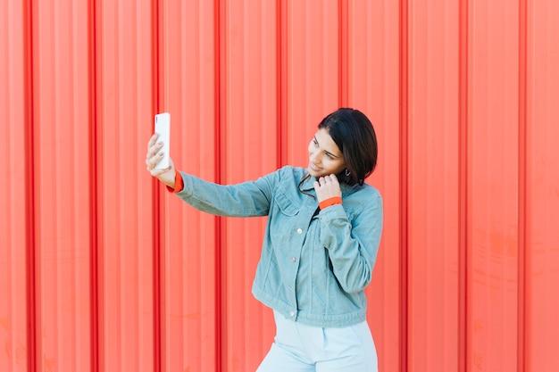 赤い金属の背景に対して携帯電話の地位にselfieを取っている若い女性