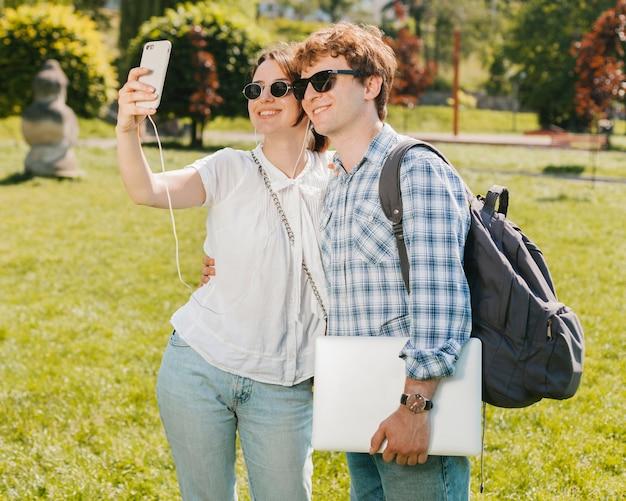 若いカップルが公園でselfieを取って