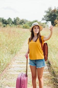 Selfieを取って荷物を持つ若い旅行者