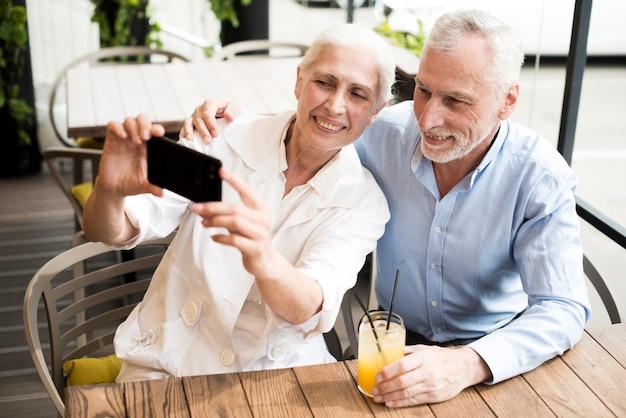 ミディアムショット老夫婦、selfieを取って