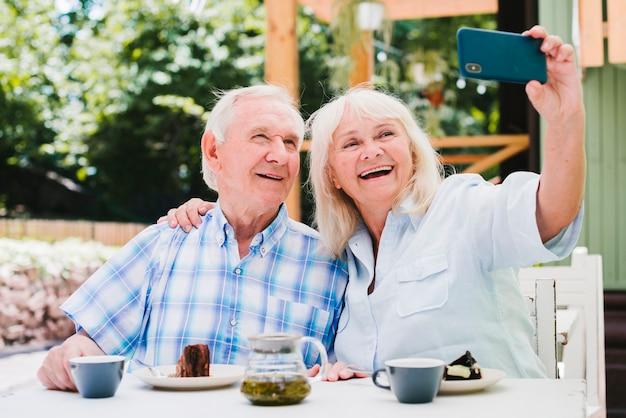 屋外テラスに座って笑顔selfieを取っている老夫婦
