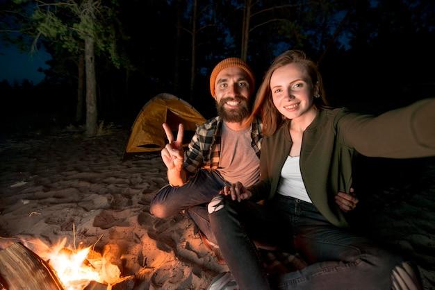 キャンプファイヤーで夜キャンプのカップルのselfie