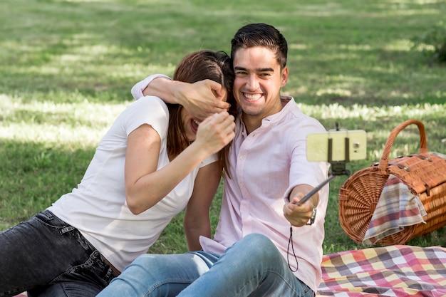 遊び心のあるカップルが公園でselfieを取って