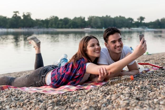 湖のそばで、selfieを取ってカップル
