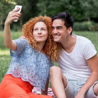 携帯電話で、selfieを取って愛のカップル