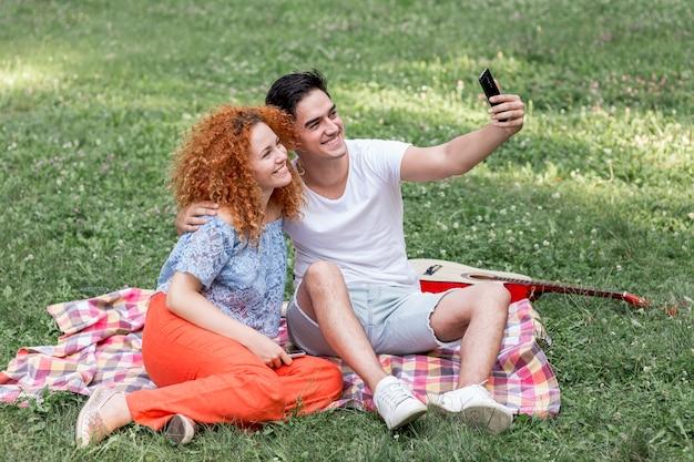 幸せなカップル、selfieを取って草の上に敷設