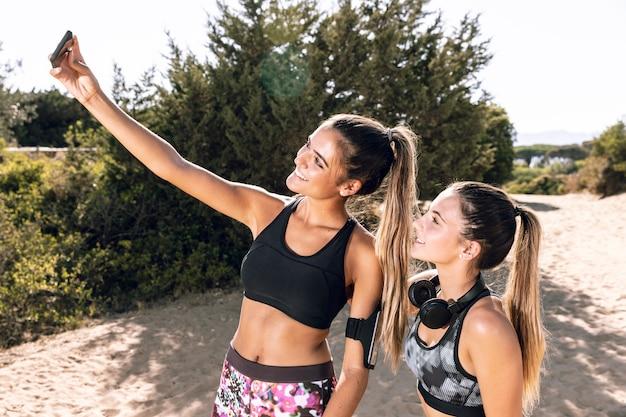 ミディアムショットスポーティな友達、selfieを引き継ぐ
