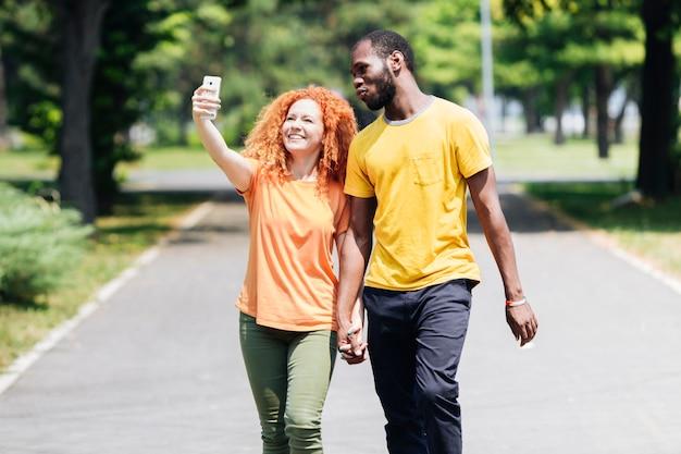 Selfieを取りながら手を繋いでいるカップル