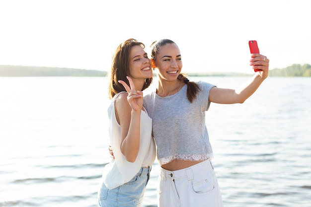 湖の横にあるselfieを取って笑顔の友達