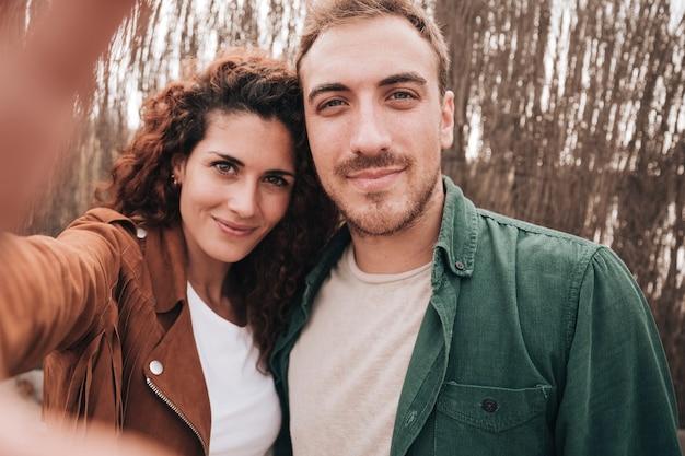 正面のカップル、selfieを取って