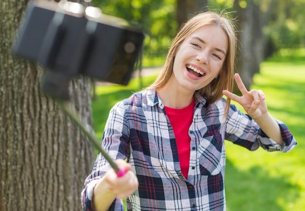 屋外で彼女の携帯電話でselfieを取っている女の子